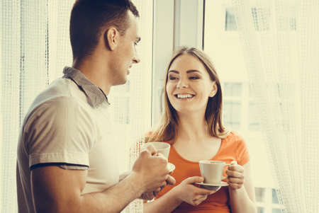 Happiness and healthy relationship concept. Attractive couple drinking tea or coffee together at home, man and woman holding cups with hot beverage at home photo