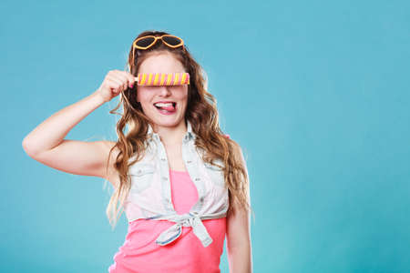 smilie: Summer holidays happiness concept. Happy joyful and cheerful young woman female model covering eyes with ice pop on blue background Stock Photo