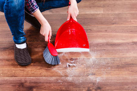 brooming: Cleanup housework concept. Closeup cleaning woman sweeping wooden floor with red small whisk broom and dustpan indoor Stock Photo