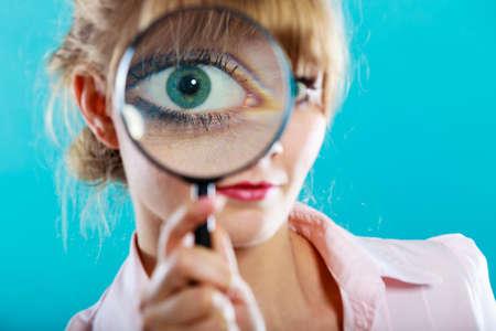 調査探査教育概念。クローズ アップ面白い女性顔、目拡大鏡ルーペを持って女の子
