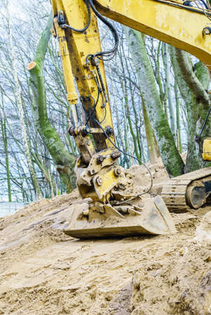 devastation: Yellow excavator dig digging trench on construction site in forest among trees. Devastation destruction of natural environment.