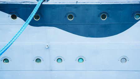docking: Closeup of blue ship with hanging mooring rope, docking line.