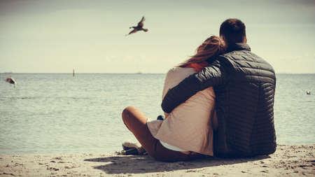 parejas: joven amante de pasar el tiempo libre juntos en la playa abrazando vista trasera