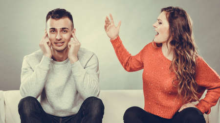 bad boy: couple having argument - conflict, bad relationships. Angry fury woman screaming man closing his ears.