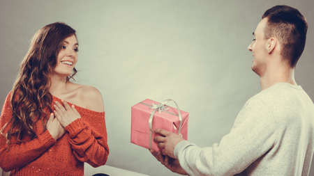 Couple and holiday concept. Handsome man surprising cheerful woman with gift box