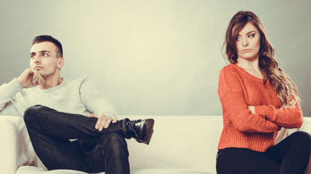 husband and wife: Bad relationship concept. Man and woman in disagreement. Young couple after quarrel sitting on sofa