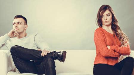marido y mujer: Mala relación de conceptos. Hombre y mujer en desacuerdo. Joven pareja después de la pelea que se sienta en el sofá Foto de archivo