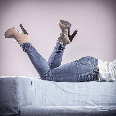 denim trousers: Fashion. Woman legs in denim trousers platform high heels shoes, girl relaxing on sofa casual style , filtered photo Stock Photo