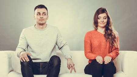 Shy woman and man. Guy sitting near attractive young woman on sofa and making hand gesture walking with finger to girl Foto de archivo