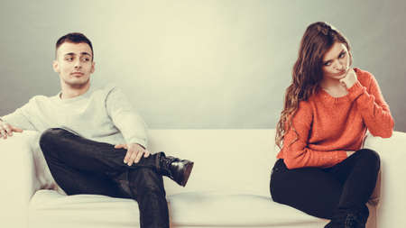 sullenly: Bad relationship concept. Man and woman in disagreement. Young couple after quarrel sitting on sofa