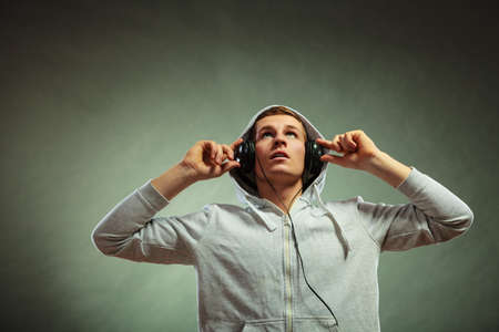 young handsome man with headphones listening to music looking up grunge background photo