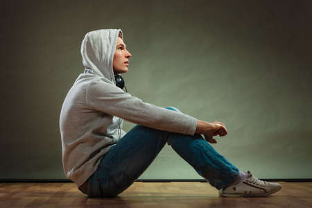 Music passion youth concept. Serious hooded man teen boy with headphones sitting daydreaming on floor grunge background photo