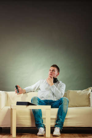 Modern technologies connection leisure concept. Young handsome man relaxing on couch with headphones smartphone and tablet at home photo