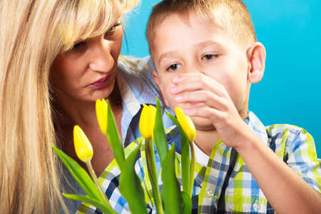 son: Boy celebrating mothers day. little child lad giving flowers yellow tulips to his mom mother studio shot on blue Stock Photo