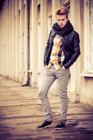 cityspace: Street fashion. Young fashionable man in full length guy with stylish haircut casual clothes posing outdoor on cityspace background. Aged tone