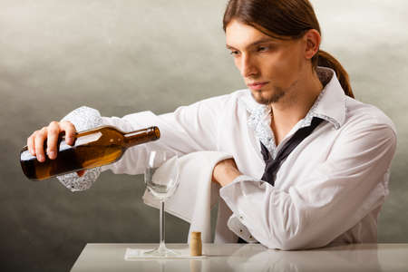 pouring wine: Male waiter or butler serving pouring wine into glass.