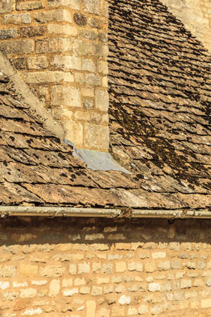 rooftiles: Architecture detail. Old stone house with chimney mossy roof tiles, village Bibury, England
