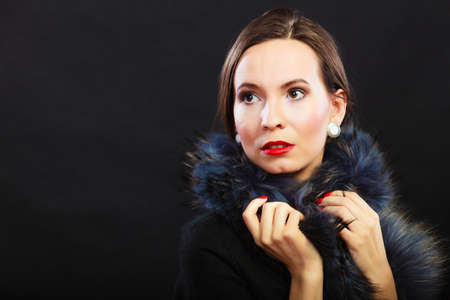 black boa: Fashion and beauty. Woman in fur coat red lips and nails, lady retro style portrait on black background Stock Photo