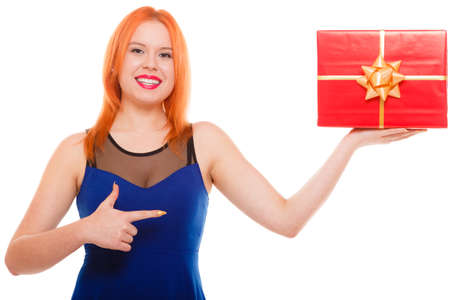 red head girl: People celebrating holidays, love and happiness concept - smiling red head girl in blue dress holds red gift box pointing studio shot isolated. Time gifts