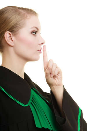 Law court or justice concept. Woman lawyer barrister wearing classic polish black green gown asking for silence isolated. Finger on lips as quiet sign symbol gesture hand.