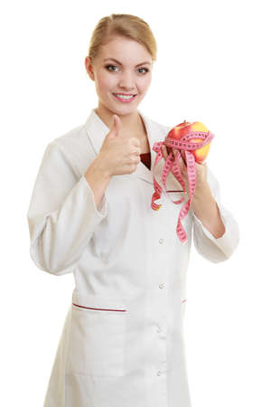 recommending: Slim down dieting concept. woman in white lab coat recommending healthy food. Doctor specialist dietitian holding fruit apple and measure tape isolated.