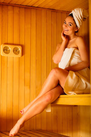 sauna: Spa beauty treatment and lifestyle relaxation concept. woman full length white towel relaxing in wooden sauna room.