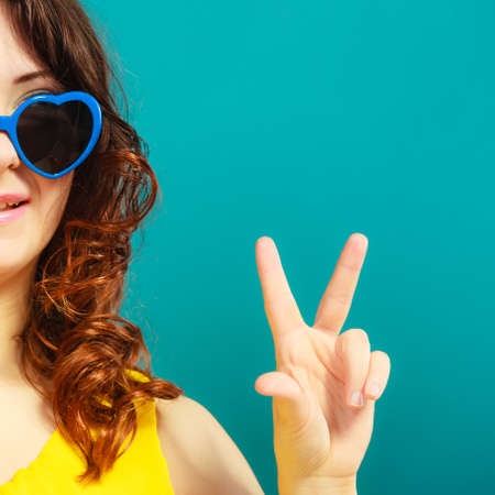Summer fashion eyes protection concept. Closeup girl long curly hair in blue heart shaped sunglasses making victory hand sign gesture photo