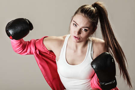 combative: Feminist and emancipation idea. Woman in male occupation, training, boxing. Fit female fitness girl doing exercise on grey background.