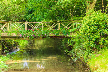 gloucestershire: Old small bridge over river stream creek in green garden. Nature and landscape.