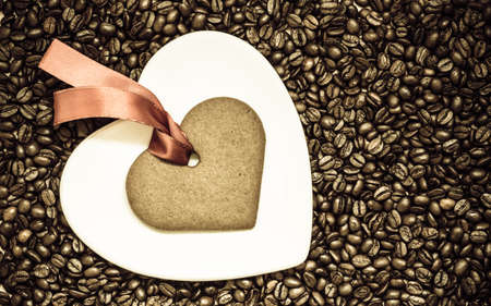 Coffee time concept. Heart shaped plate and cookie gingerbread with red robbon on coffee beans background. Top view
