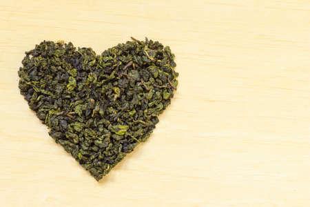 essen und trinken: Di�t-Gesundheitskonzept. Gr�ner Tee Herz auf h�lzernen Oberfl�che geformt. Gesunde Ern�hrung Getr�nk f�r niedrigere Herz-Risiko