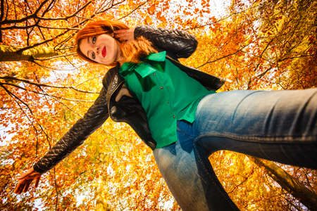unusual angle: Season and happy people concept. Unusual low angle view of young happy woman in autumn park. Beauty redhaired girl relaxing playing in flying outdoor