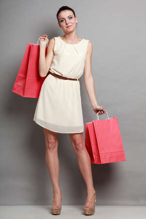shopaholism: Sale and retail. Young woman girl with red shopping bags in hands on grey background in studio.