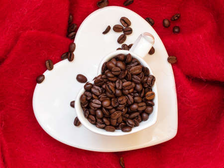 love pic: Coffee klatsch java concept. Heart shaped white cup filled with roasted coffee beans on red cloth background Stock Photo