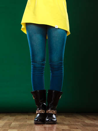 denim trousers: Fashion. Woman legs in denim trousers black boots casual style on green
