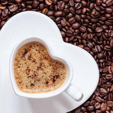 cappucino: Hot beverage. White coffee cup heart shaped with cappucino latte on roasted beans background