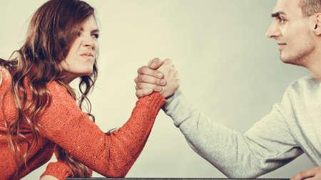 Asociación relación de conceptos. Novia se enfrenta a su novio. La mujer y el hombre del brazo de lucha desafío entre la joven pareja