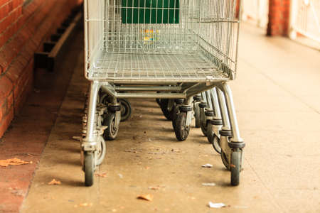 retail: Row of empty shopping cart trolley. Market grocery shop and retail concept. Outdoor.