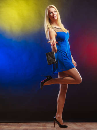 dancing club: Fashion elegant outfit. Stylish woman fashionable blonde girl full length with black rivet leather handbag bag in night club dancing.