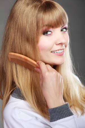 combing: Fashion beauty and haircare concept. Closeup blonde woman refreshing her hairstyle girl combing hair with wooden comb gray background Stock Photo