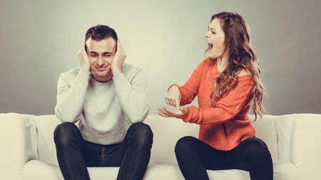 カップルは引数 - を持つ競合、悪い関係。怒っている激怒の女性叫んで人を彼の耳を閉じるします。 写真素材