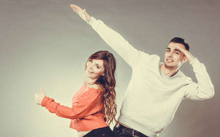 oncept: Love friendship and happiness oncept. Smiling young couple having fun, happy man and woman studio shot on gray