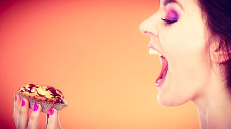 mouth  open: Bakery, sweet food and people concept. Woman face profile wide open mouth holds cake cupcake in hand orange background Stock Photo