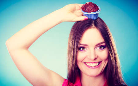 indulging: Sweet food sugar make us happy. Smiling crazy woman holds cake chocolate muffin on head blue background Stock Photo