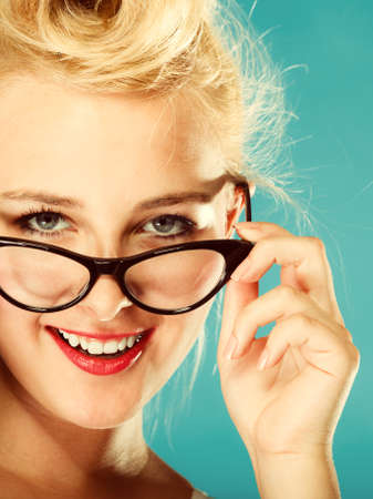 oculist: Optometrist, oculist and ophthalmologist concept. Young blonde retro pin up smiling woman with eyeglasses on blue background in studio.