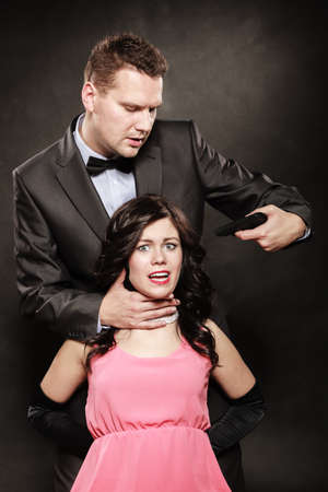 intimidating: Scene of violence with firearm between men and women. Elegant man holding gun against sitting lady on black and grey background in studio. Stock Photo