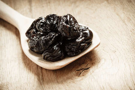 prunes: Healthy food, good cuisine. Closeup dried plums prunes fruits on wooden spoon rustic table background