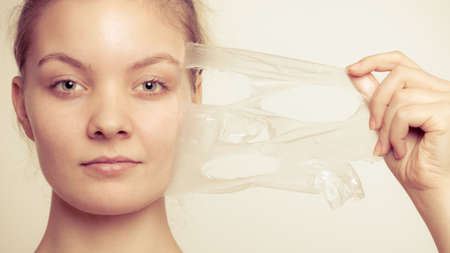 Beauty skin care cosmetics and health concept. Closeup young woman face, girl removing facial peel off mask on gray. Peeling