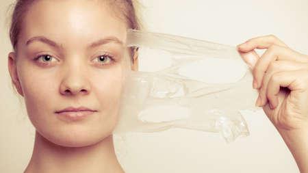 tratamientos faciales: Belleza cosm�ticos cuidado de la piel y el concepto de salud. Primer rostro de mujer joven, muchacha que quita facial mascarilla exfoliante en gris. Descamaci�n Foto de archivo