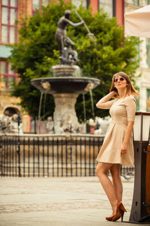 neptun: Holidays and tourism concept. Full length pretty woman in elegant dress outdoor on the street of old town european city Gdansk Danzig Neptune fountain Poland Stock Photo